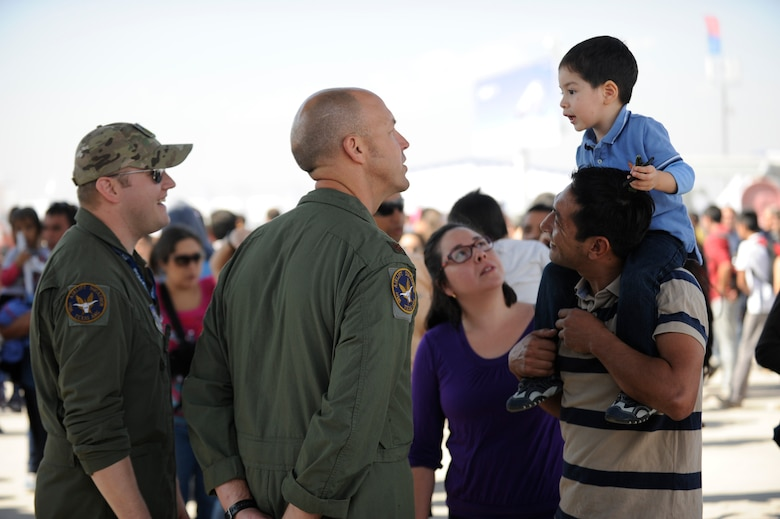 Tech. Sgt. Brian Krause and Maj Josh Ritzmann, members of the 136th Airlift Wing, attempt to communicate with a young local visitor enjoying FIDAE (Feria Internacional del Aire y del Espacio), an international trade exhibition air and space show, in Santiago, Chile, March 29, 2014. Krause and Ritzmann were in Chile with other members of the Texas Air National Guard for a subject matter expert exchange through the National Guard Bureau's State Partnership Program. (U.S. Air National Guard photo by Senior Master Sgt. Miguel Arellano / Released)