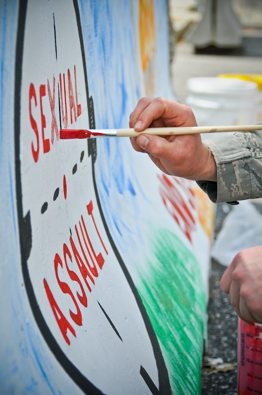 """A picture of U.S. Air Force Staff Sgt. Anthony Foster from the 177th Fighter Wing paints the words """"sexual assault"""" inside of a painting of a cross hair."""