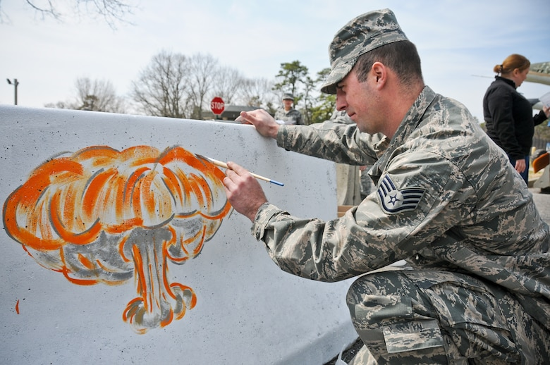 A picture of U.S. Air Force Staff Sgt. Anthony Foster from the 177th Fighter Wing painting a mushroom cloud onto a barrier.