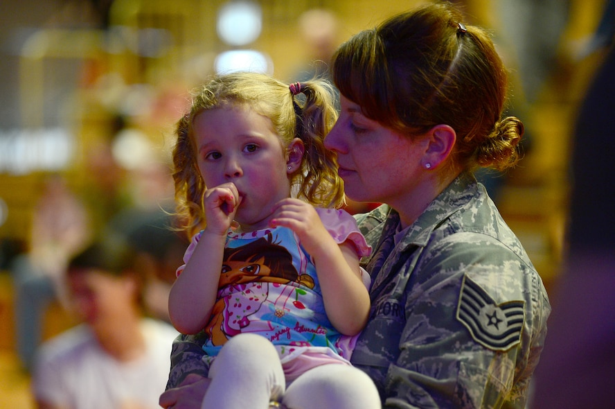 U.S. Air Force Tech. Sgt. Erika Stein, 52nd Fighter Wing executive assistant to the command chief and from Pittsburgh, holds her daughter, Chloe, during the Imagination Movers concert at the Skelton Memorial Fitness Center, Spangdahlem Air Base, Germany, April 7, 2014. The band performed for approximately one hour before signing autographs for the children after the show. (U.S. Air Force photo by Airman 1st Class Kyle Gese/Released)