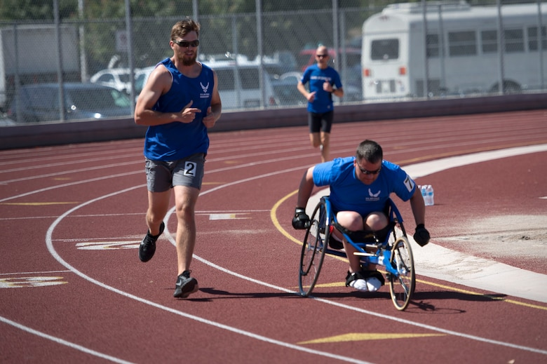 Airmen race to the finish line during the track and field portion of the Air Force Trials April 8, 2014, at Rancho High School in Las Vegas, Nev. The Air Force Trials give injured, ill and wounded Airmen a chance to compete in Paralympic-style events.  (U.S. Air Force photo/Senior Airman Jette Carr)