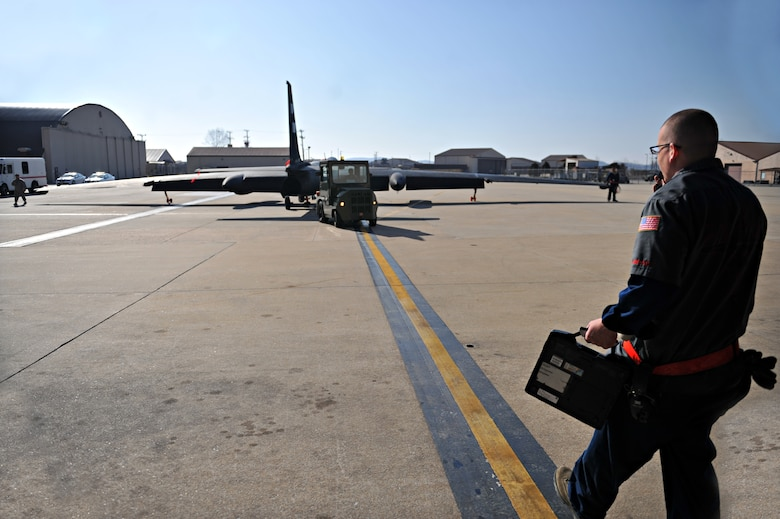 A crew chief assigned to the 5th Reconnaissance Squadron marshals a U-2 Dragon Lady into a hangar after a mission at Osan Air Base, Republic of Korea, March 10, 2014. There are members from more than 20 different Air Force Specialty Codes in the 5th RS. (U.S. Air Force photos/Senior Airman Siuta B. Ika)