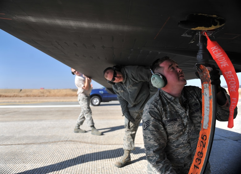 Members of the 5th Reconnaissance Squadron pogo team place a pogo under the wing of a U-2 Dragon Lady after a mission at Osan Air Base, Republic of Korea, March 10, 2014. The pogo team follows behind the U-2 during every launch and landing to clean up and install the pogos which help the U-2 maneuver easier while on the ground. (U.S. Air Force photo/Senior Airman Siuta B. Ika)
