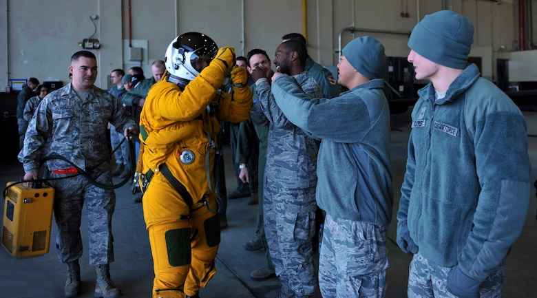 Maj. David (last name withheld due to operational security constraints), 5th Reconnaissance Squadron U-2 Dragon Lady pilot, fist bumps other 5th RS members before flying a mission at Osan Air Base, Republic of Korea, March 10, 2014. Before every mission, the team comes together to see the pilot off and then welcome him back upon his return. (U.S. Air Force photo/Senior Airman Siuta B. Ika)