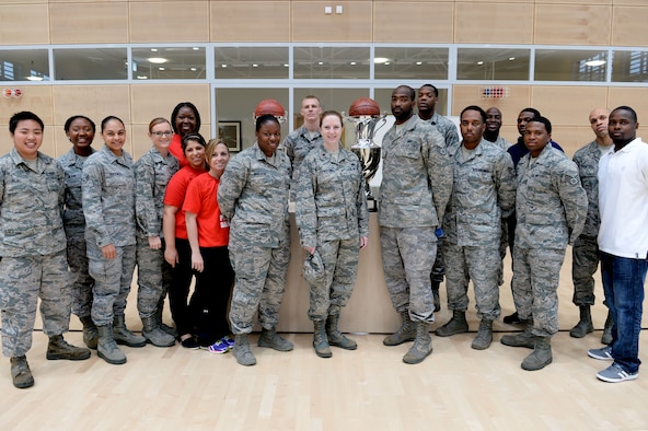 The Spangdahlem's men and women's basketball teams pose with their first-place trophies at the Eifel Powerhaus April 7, 2014 after competing in the 2014 United States Army Garrison European International Basketball Tournament March 21-23. The teams earned the number one spot in a total of five tournaments and a combined total of 60 games scoring more than 2,200 points. (U.S. Air Force photo by Senior Airman Alexis Siekert/Released)