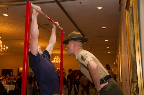 Staff Sgt. Robert M. Surozenski, a Drill Instructor from Marine Corps Recruit Depot San Diego, motivates a poolee during a partial Initial Strength Test at Recruiting Station Milwaukee's Family Nights pool function, Apr. 5.  Family Nights give poolees their first glimpse into Marine Corps recruit training and allow family members to voice any questions or concerns they may have about recruit training.