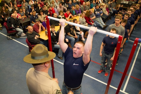 Morgan Daly, a poolee from Recruiting Substation Green Bay, performs pull-ups during a partial Initial Strength Test at RSS Green Bay's Family Night pool function, Apr. 3.  Family Nights give poolees their first glimpse into Marine Corps recruit training and allow family members to voice any questions or concerns they may have about recruit training.
