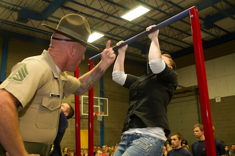 Staff Sgt. Nicholas A. Carrel, a Drill Instructor from Marine Corps Recruit Depot San Diego, motivates a poolee during a partial Initial Strength Test at Recruiting Substation Green Bay's Family Nights pool function, Apr. 3.  Family Nights give poolees their first glimpse into Marine Corps recruit training and allow family members to voice any questions or concerns they may have about recruit training.