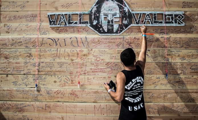 Richard Hernandez, a Marine with the 15th Marine Expeditionary Unit, writes the names of three fallen Marines on the Wall of Valor during a Spartan Race event in Las Vegas, April 5, 2014. Seven Marines from the 15th MEU, and other units aboard Marine Corps Base Camp Pendleton, ran the race in memory of the Marines who died in a car accident in February 2012.
