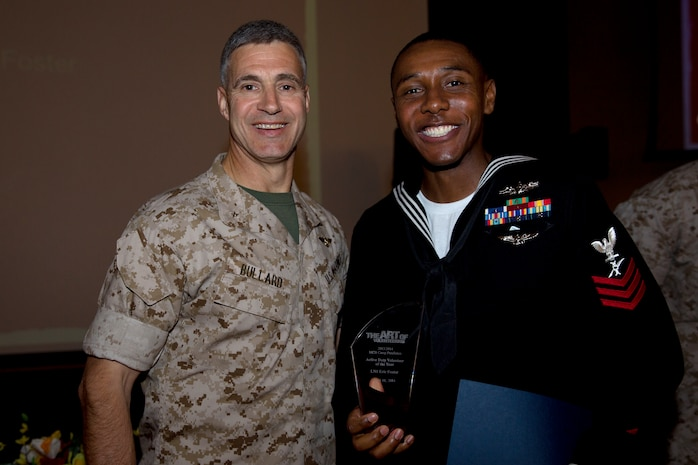 Petty Officer 1st Class Eric Foster, recipient of the Active Duty Volunteer of the Year award, poses with Brig. Gen. John W. Bullard, commanding general of Marine Corps Installations-West, during the 2014 Volunteer Recognition Ceremony at the Pacific Views Event Center April 10. More than 6,000 military and civilian volunteers from several units on Camp Pendleton accumulated a total of 110,461 hours of volunteer service in 2013.