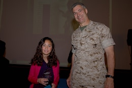 Cara, the 9-year-old recipient of the Youth Volunteer of the Year award, poses with Brig. Gen. John W. Bullard, commanding general of Marine Corps Installations-West, during the 2014 Volunteer Recognition Ceremony at the Pacific Views Event Center April 10.More than 6,000 military and civilian volunteers from several units on Camp Pendleton accumulated a total of 110,461 hours of volunteer service in 2013.
