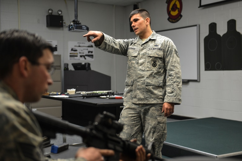 Staff Sgt. Christopher Hoffman, 627th Security Forces Squadron combat arms instructor educates McChord Field Airmen proper technique for reloading the M-4 carbine rifle, April 9, 2014 at Joint Base Lewis-McChord, Wash. In the classroom, McChord Field Airmen gain in-depth knowledge of the M-4 carbine rifle including safety, inspecting, and cleaning. (U.S. Air Force photo/Staff Sgt. Russ Jackson)