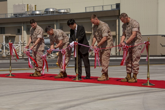 From left to right, Col. Robert V. Boucher, commanding officer of Marine Corps Air Station Iwakuni, Japan, Maj. Gen. Juan G. Ayala, commander of Marine Corps Installations Command, Takafumi Fujii, director general of the Chugoku-Shikoku Defense Bureau, Brig. Gen. Steven Rudder, commanding general of 1st Marine Aircraft Wing, and Col. Hunter Hobson, commanding officer of Marine Aircraft Group 12, cut a ceremonial ribbon signifying the official opening of new facilities during the MAG-12 and Marine Aviation Logistics Squadron 12 ribbon cutting ceremony aboard station March 27, 2014. The Defense Policy Review Initiative built the new facilities as part of the ongoing construction focused on rebuilding 77 percent of the station.