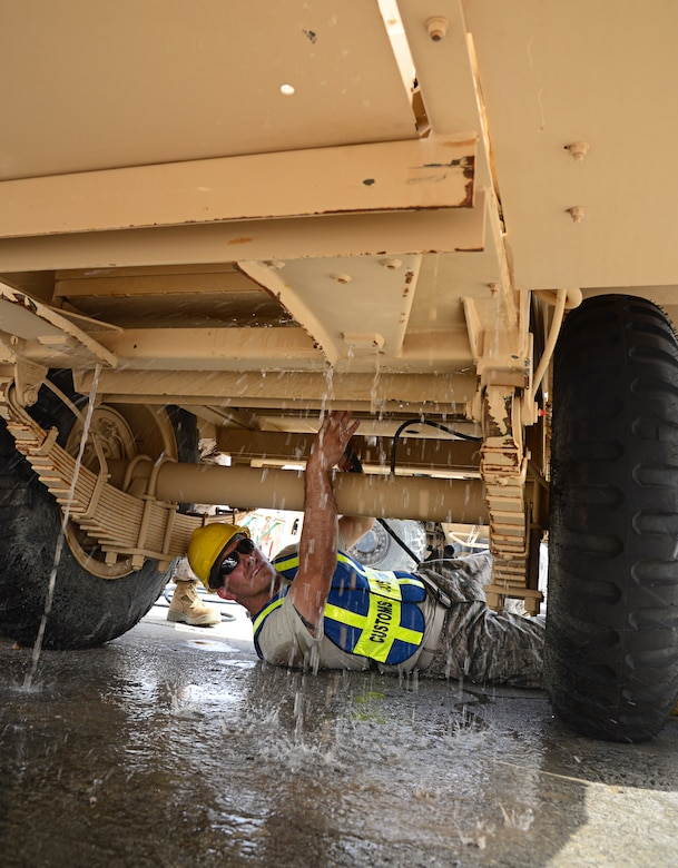 Tech. Sgt. Jacob Phillips removes agricultural hazards from a generator during a vehicle decontamination April 1, 2014, in Southwest Asia. The 387th Air Expeditionary Squadron is preparing the Marine Corps' 2nd Law Enforcement Battalion to assume the U.S. Central Command's Customs Operations mission. Phillips is a 387th AES customs agent. (U.S. Air Force photo/Senior Airman Desiree W. Moye)