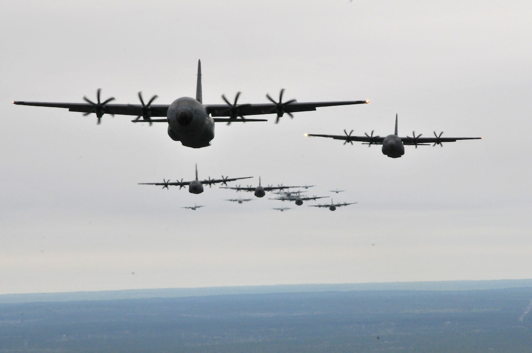 C-130J Hercules and WC-130J Hercules fly in formation during an Operation Surge Capacity exercise over the Mississippi Gulf Coast region April, 5, 2014. Aircraft from the 815th and 345th Airlift Squadrons and 53rd Weather Reconnaissance Squadron participated in the large-scale training exercise designed to test the 403rd Wing's ability to launch and recover a large formation of aircraft and to execute airdrops. The C-130s are assigned to the 403rd Wing at Keesler Air Force Base, Miss. (U.S. Air Force photo/Senior Airman Nicholas Monteleone)
