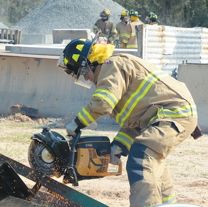 A fireman cuts debris to be repurposed as a tool to assist in the rescue of a simulated victim April 1 during Twisting Thunder 2014 at Marine Corps Logistics Base Albany.