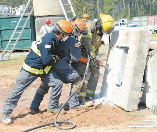A team works to reach a simulated trapped victim by creating an opening in a slab of concrete during exercise Twisting Thunder 2014 aboard Marine Corps Logistics Base Albany, April 1. This scenario was part of a two-day destructive weather exercise.