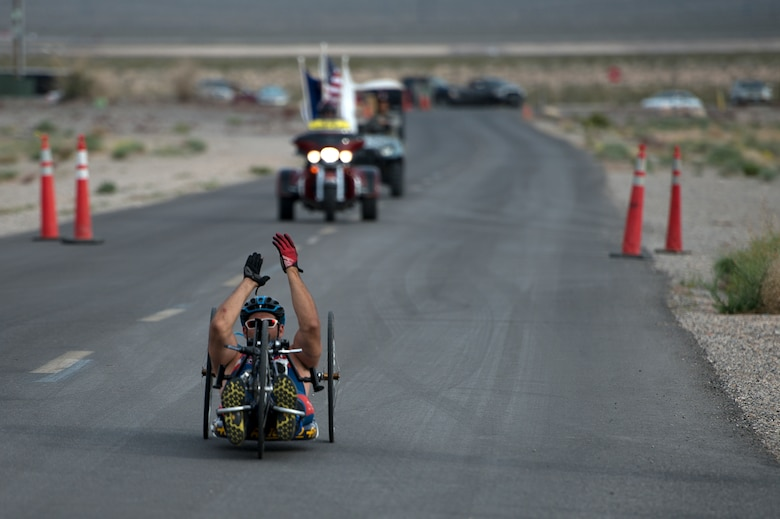 Ryan Pinney claps as he nears the finish line April 9, 2014, during a cycling race in the the Air Force Trials at Nellis Air Force Base, Nev. Pinney competed against other Air Force wounded warriors during the 6-mile men's handcycle heat. (U.S. Air Force photo/Senior Airman Jette Carr)