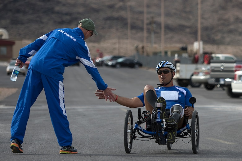 Christopher Aguilera cycles by Mike Sanders to receive a high-five after he finished the race April 9, 2014, during the Air Force Trials at Nellis Air Force Base, Nev. Aguilera, and Air Force wounded warrior, placed first in his category during the cycling completion. (U.S. Air Force photo/Senior Airman Jette Carr)