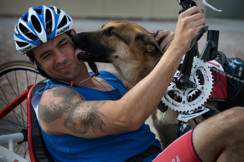 August O'Neill is kissed by his service dog, Kai, April 9, 2014, during the cycling portion of the Air Force Trials at Nellis Air Force Base, Nev.  O'Neill, an Air Force wounded warrior, competed in the 6-mile men's handcycle heat with four others.  (U.S. Air Force photo/Senior Airman Jette Carr)