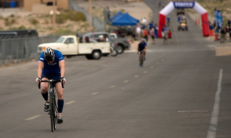 Cyclists pass through the finish line during the 18-mile men's bicycle open April 9, 2014, at Nellis Air Force Base, Nev.  The cyclists circled a two mile loop based upon how many miles they needed to accomplish for their particular race.  (U.S. Air Force photo/Senior Airman Jette Carr)