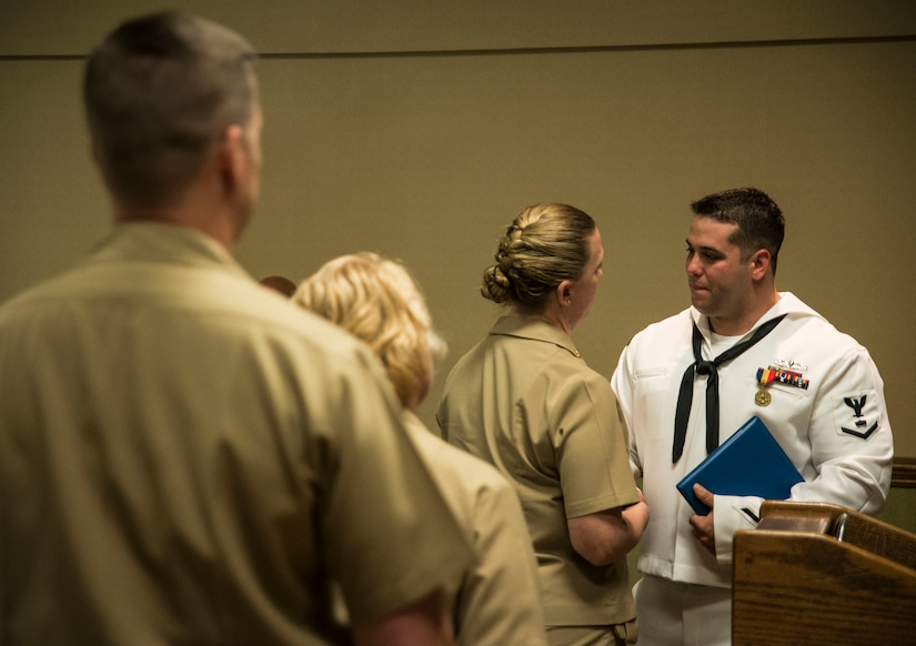 Petty Officer 3rd Class Travis Kirckof is congratulated by his shipmates after receiving the Navy and Marine Corps Medal April 11, 2014, at Joint Base Charleston – Weapons Station, S.C. Kirckof received the medal for his heroic actions while serving as a Search and Rescue Swimmer on USS Guardian (MCM 5), where he helped 46 of his shipmates to safety after the Guardian ran aground on a reef in the Sulu Sea, Jan. 17, 2013. (U.S. Air Force photo/Senior Airman Dennis Sloan)