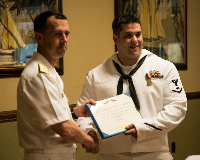 Admiral John Richardson, Director of the Naval Nuclear Propulsion Program, presents Petty Officer 3rd Class Travis Kirckof the medal citation awarding Kirckof the Navy and Marine Corps Medal April 11, 2014, at Joint Base Charleston – Weapons Station. Kirckof received the medal for his heroic actions while serving as a Search and Rescue Swimmer on USS Guardian (MCM 5), where he helped 46 of his shipmates to safety after the Guardian ran aground on a reef in the Sulu Sea, Jan. 17, 2013. (U.S. Air Force photo/Senior Airman Dennis Sloan)