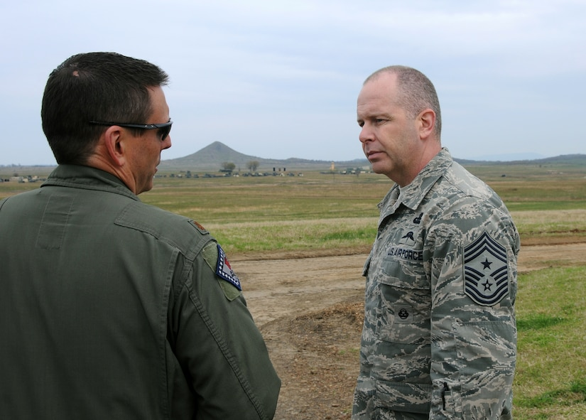 Air National Guard Command Chief Master Sgt. James W. Hotaling speaks with Maj. Doug Davis, 188th Fighter Wing Detachment 1 Razorback Range commander, during his visit to the 188th Fighter Wing April 5, 2014. Hotaling spoke with enlisted Airmen across the base about professionalism, resilience and recognition, and observed close air support training at the range. (U.S. Air National Guard photo by Senior Airman John Hillier/released)