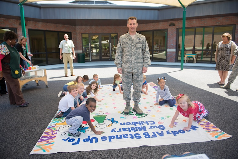 U.S. Air Force Col. Chad Franks, 23d Wing commander, helps paint a child abuse awareness poster with Child Development Center children of military service members April 9, 2014, at Moody Air Force Base, Ga. The poster was donated by the 23d Civil Engineer Squadron.