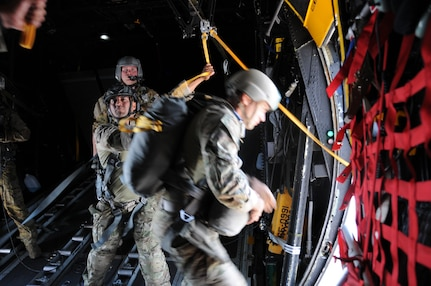 A 7th Special Forces Group jumpmaster directs paratroopers as they depart from a C-130 Hercules aircraft during a joint airborne operations training jump with the Honduran military at Soto Cano Air Base, Honduras on April 3, 2014.  .  The 1,500 foot static line jump allowed members from both nations to retain currency, while also strengthening the relationship between the U.S. and Honduran forces.  (Photo by U. S. Air National Guard Capt. Steven Stubbs)