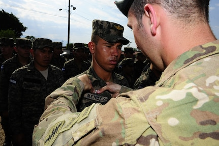 A 7th Special Forces Group paratrooper pins a set of jump wings on a Honduran 2nd Combat Airborne Infantry Battalion paratrooper during a wing exchange after performing joint airborne operations training consisting of jumping from a C-130 Hercules aircraft at Soto Cano Air Base, Honduras on April 3, 2014.  The 1,500 foot static line jump allowed members from both nations to retain currency, while also strengthening the relationship between the U.S. and Honduran forces.  (Photo by Martin Chahin)