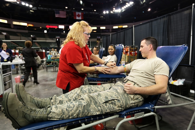 U.S. Air Force Staff Sgt. David Savino, right, watches as a nurse identifies a vein from where blood will be drawn. The 108th Wing finance management journeyman was part of the approximate 200 Soldiers and Airmen from the New Jersey National Guard who volunteered to donate blood at the Super Community Blood Drive at the Sun National Bank Center in Trenton, N.J., Jan. 14, 2014. (NJDMAVA photo by Tech. Sgt. Armando Vasquez/Released)