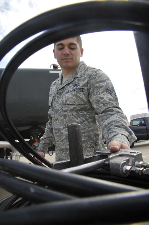 """U.S. Air Force Airman 1st Class Joshua Reynolds, 509th Logistics Readiness Squadron fuels distribution technician, puts down a hose reel at Whiteman Air Force Base, Mo. April 1, 2014.  The reel is used to """"run """"the hose back into the R11 truck for safe and security purposes. (U.S. Air Force photo by Airman 1st Class Keenan Berry/Released)"""