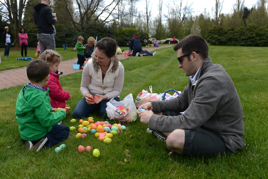 Tech Sgt. Zachery Smith (right), Western Air Defense Sector air surveillance technician, and his family search their Easter eggs for a winning ticket at the 5/6 Junior NCO Council's free Easter egg hunt, April 12, 2014 at Joint Base Lewis-McChord, Wash. Children who found Easter eggs with winning tickets received Easter baskets or gift cards depending on their age group. (U.S. Air Force photo/Airman 1st Class Jacob Jimenez)