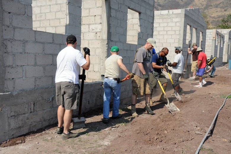 Twenty-one Joint Task Force-Bravo service members filled trenches, leveled ground and shoveled dirt at the Ajuterique Housing Project helping several Honduran families get closer to moving into their new homes April 5, 2014.  In conjunction with the Honduras Habit for Humanity, Siguatepeque region, the Municipality of Ajuterique and the Civil-Military Operations office at JTF-Bravo, these service members volunteered their labor to assist in the building of homes in the Ajuterique community.  The two-phased project includes building 38 two-bedroom, one-bath homes for low-income Hondurans who can afford to construct a home but doesn't own the land to build on. (Photo by U. S. Air National Guard Capt. Steven Stubbs)