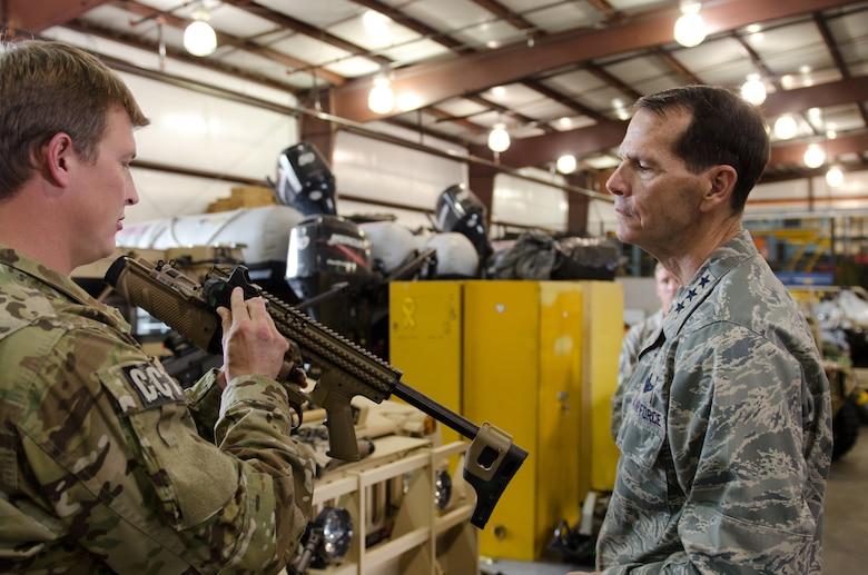 Tech. Sgt. Ben Pelster, a combat controller from the 123rd Special Tactics Squadron, shows an MK-13 40mm grenade launcher to Lt. Gen. Stanley E. Clarke III, director of the Air National Guard, during a tour of the Kentucky Air National Guard Base in Louisville, Ky., April 11, 2014. Clarke visited with Airmen from across the 123rd Airlift Wing and examined mission capabilities ranging from contingency response to special tactics. (U.S. Air National Guard photo by Airman 1st Class Joshua Horton)