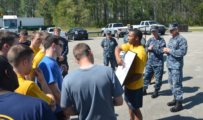 Commander Charles Phillip, Naval Munitions Command commanding officer (right), and Master Chief Petty Officer Jason Roach, NMC command master chief, look on as NMC Sailors are briefed on the route they will be running for the command's Sexual Assault Awareness Month 5K run April 10, 2014, at Joint Base Charleston – Weapons Station, S.C.  The command event was organized to help raise awareness of the issue of sexual assault. (U.S. Air Force photo/Eric Sesit)