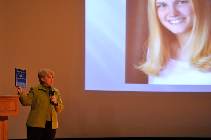 Mary Lauterbach holds up the Inspector General's report about her daughter's sexual assault during her speech to members of Joint Base Charleston during a Sexual Assault Awareness Month event April 11, 2014, at the Air Base Theater on JB Charleston, S.C. Lauterbach's daughter, U.S. Marine Lance Cpl. Maria Lauterbach, was sexually assaulted and murdered while on active duty in 2007. (U.S. Air Force photo/Staff Sgt. Renae Pittman)