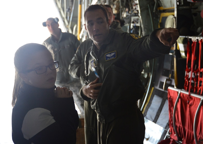 Looking down the belly of the C-130H, Tori Pilletere, 12, gets a fully immersive look and explanation of the capabilities of the aircraft by 1st Lt. Paul Bolduc, a pilot with the 118th Airlift Squadron, during a tour of the Bradley Air National Guard Base, East Granby, Conn., April 5,2014. The tour of the C-130H was part of the Connecticut Youth Council's initiative to get more Air Guard youth involved with the council. (U.S. Air National Guard photo by Tech. Sgt. Joshua Mead)