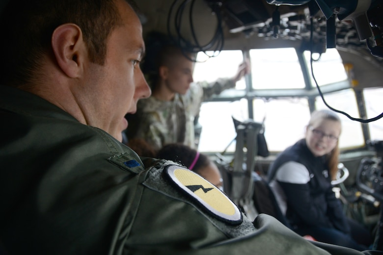 1st Lt. Paul Bolduc, C-130H pilot with the 118th Airlift Squadron, points out and explains the small emergency exit window, among other things, located in the cockpit of a C-130H to a group of Connecticut Air Guard youth at Bradley Air National Guard Base, East Granby, on April 5, 2014. In the background two of the youth participants, Cody Kirkland, 16, and Tori Pilletere, 12, ask questions and get a feel for what it's like to be a pilot as a Flying Yankee. (U.S. Air National Guard photo by Tech. Sgt. Joshua Mead)