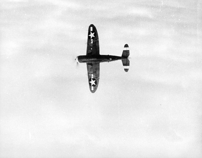 A Republic P-47 Thunderbolt, clean with no bombs or external tanks carried banks away from a camera plane in the European Theater of Operations in World War II.  The national insignia on the bottom of both wings was an ETO measure to help Allied personnel on the ground identify it as a friendly aircraft.  (Source:  142FW History Archives)