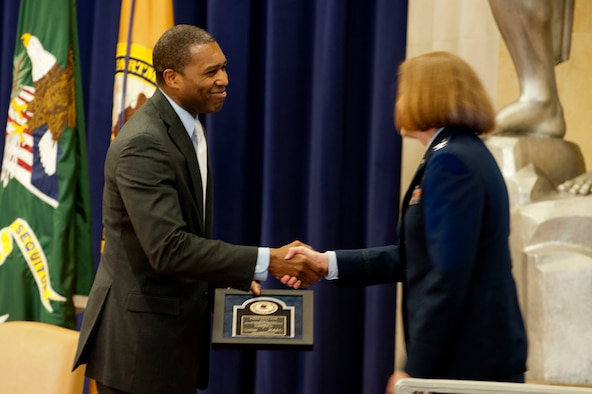 Tony West (left) presents Col. Dawn Hankins with the Federal Service Award during the 2014 Justice Department's National Crime Victims' Rights Service Awards ceremony, April 9, 2014, at the Department of Justice, Washington D.C. West is the associate attorney general of the United States. Hawkins is the chief of the Air Force Special Victims' Counsel Program  (U.S. Air Force photo/Staff Sgt. Carlin Leslie)