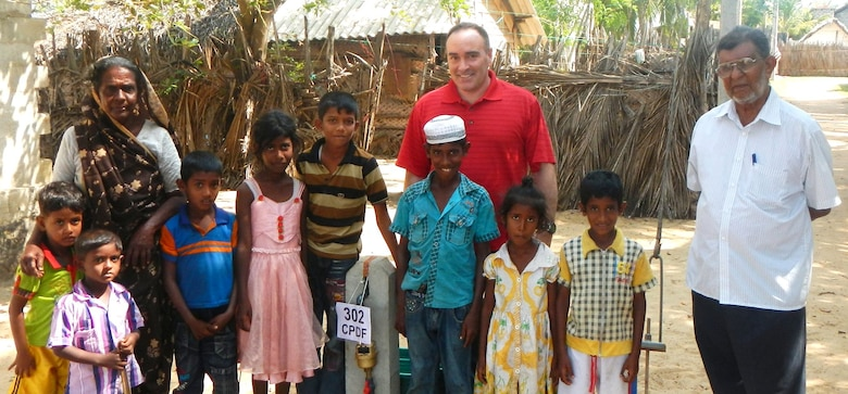 "Col. Christopher Lestochi, district commander, poses with a family benefiting from the Puttalam water project. The U.S. Army Corps of Engineers?"" Alaska District, U.S. Pacific Command and the U.S. Agency for International Aid are coordinating an effort to connect 371 family households to the town's water supply."