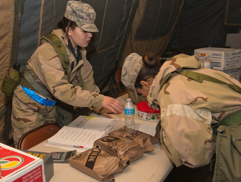 Airman 1st Class Kristina Hampton, 366th Force Support Squadron food services apprentice, sells prepackaged food known as Meals Ready to Eat, or MREs, to Airman Andrea Dunphy, 366th Force Support Squadron food services apprentice, during the Sharpshooter 14-02 exercise April 15, 2014, Mountain Home Air Force Base, Idaho. During the duration of the exercise, Airmen have the opportunity to purchase MRE's. (U.S. Air Force photo by Airman 1st Class Malissa Lott)