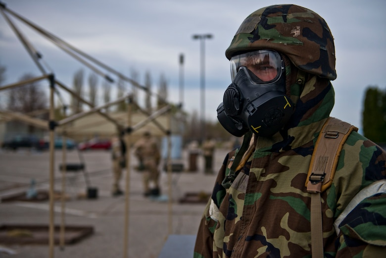 Senior Airman Ryan Gramlich, Contamination Control Area personnel, supervises simulated decontamination proceedures during the Sharpshooter 14-02 exercise April 15, 2014, Mountain Home Air Force Base, Idaho. When Airmen's gear is contaminated, they are guided through a series of stations in the CCA. (U.S. Air Force photo by Airman 1st Class Malissa Lott)