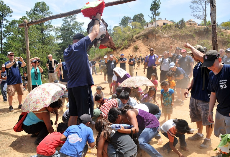 Children from the village of Picacho, Honduras scramble to gather candy from a pinata.  More than 130 members of Joint Task Force-Bravo completed a 6.2 mile round trip hike to deliver more than 3,000 pounds of food and supplies to families in need in the mountain village, April 12, 2014. During the more than three mile trek up the mountain, Task Force members made an elevation gain of 1,600 feet while carrying more than 25 pounds of supplies each. The food and supplies were all purchased with donations made by the members of Joint Task Force-Bravo. (Photo by Ana Fonseca)
