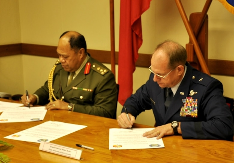 Brig. Gen. Tau'aika Uta'atu, left, the commander of Tonga's armed forces, and Nevada Adjutant General Brig. Gen. Bill Burks, sign the documents to enter their respective parties into the State Partnership Program during a formal signing ceremony held at Armed Forces Headquarters in Nuku'alofa, Tonga, on April 11. The State Partnership Program now features 68 partnerships involving 74 nations around the world.  Photo by Maj. Dennis Fournier, Joint Force Headquarters Public Affairs