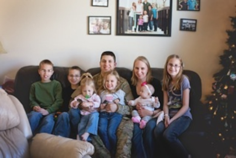 Master Sgt. Zachery Mleko, Air Reserve Personnel Center system requirements analyst, and his wife Jamie Mleko, spend time with their children upon his return from deployment in December, 2013. (Courtesy photo)