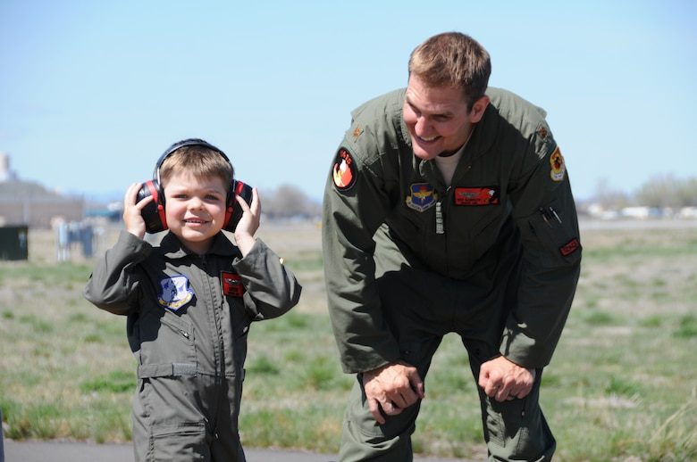 """Miles Scott, call sign,""""Batkid"""", reported for duty at the 173rd Fighter Wing in Klamath Falls, Ore., April 10, 2014. Scott is in remission from leukemia and had the opportunity to be a part of the Fighter Pilot for a Day program hosted by the 114th Fighter Squadron.  He donned a flight suit and helmet and Maj. Richard Giampietri, F-15 instructor pilot, escorted Scott to watch take-offs up close and personal, sit in the cockpit of a jet, and meet the crew chief and other maintenance personnel. (U.S. Air Force photo by Tech. Sgt. Jefferson Thompson/released)"""