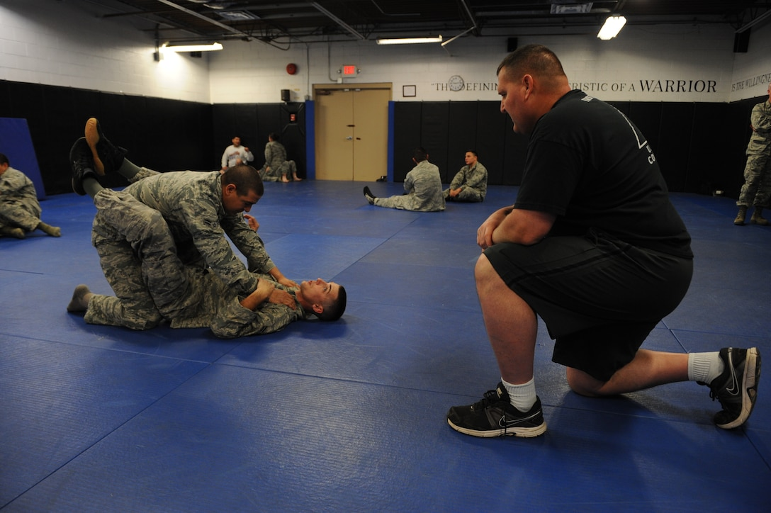 """Army instructor Sgt. Major Mark Ruffe observes  Airman 1st Class Stephen Anderson (bottom) forcing Airman 1st Class Jordan Apalategui (top) into a """"guard position,"""" thereby giving Anderson dominancy in the fight. The two security forces specialists were part of an intense 5-day, Army National Guard-instructed training event titled Basic Combative Course at the Western Army National Guard Aviation Training Site gym in Marana, Ariz., March 17-21."""